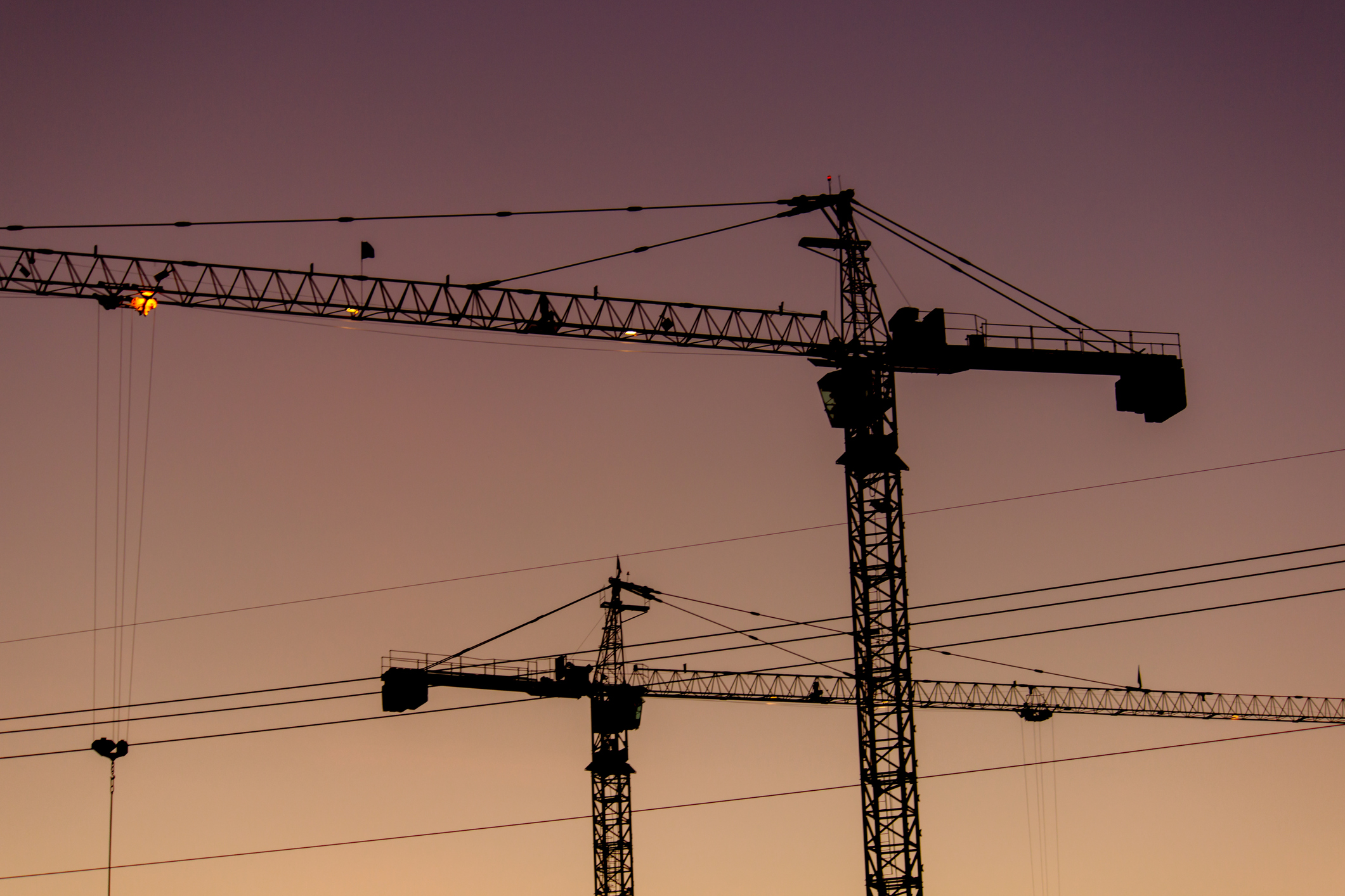 Two construction cranes parallel to each other